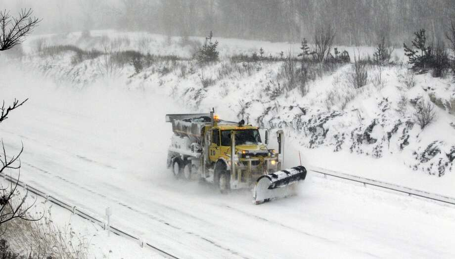 A plow moves along a empty stretch of the New York State thruway in Hamburg,N.Y., after it was closed down due to high winds, Tuesday, Jan. 7, 2014. (AP Photo/The Buffalo News, Harry Scull Jr.) Photo: Harry Scull, Jr., Associated Press