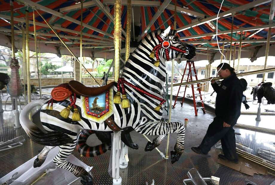 A San Antonio Zoo worker carries parts as the new carousel in the Zootennial Plaza is assembled. The carousel is being built to commemorate the Zoo's 100th birthday, Wednesday, Jan. 8, 2013. Photo: BOB OWEN, San Antonio Express-News / © 2012 San Antonio Express-News