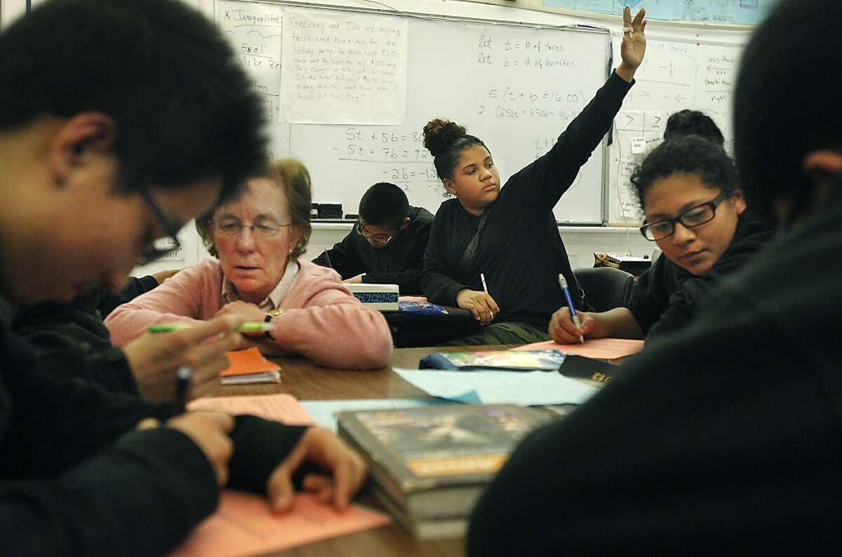 Tiara Vandigriff, 13, center, raises her hand for help while students work around her, from left, Simon Wong, 13, Johnny Yu, 14, (not visible) gets help from Instructional Reform Facilitator Ann Lyon, with Helen Villanueva, 13, at right, during an 8th grade Algebra class December 19, 2013 at James Denman Middle School.