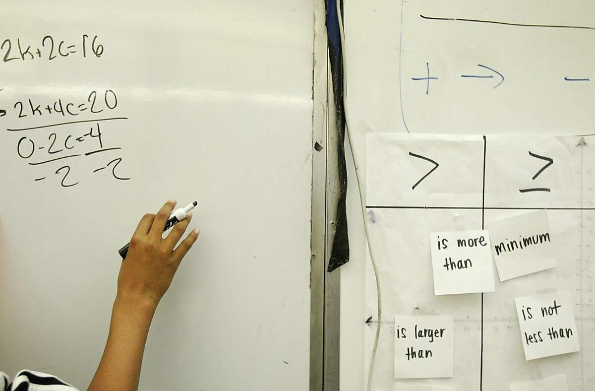 Antonio Cole, 13, writes an example of a completed class problem on the white board during an 8th grade Algebra class December 19, 2013 at James Denman Middle School.