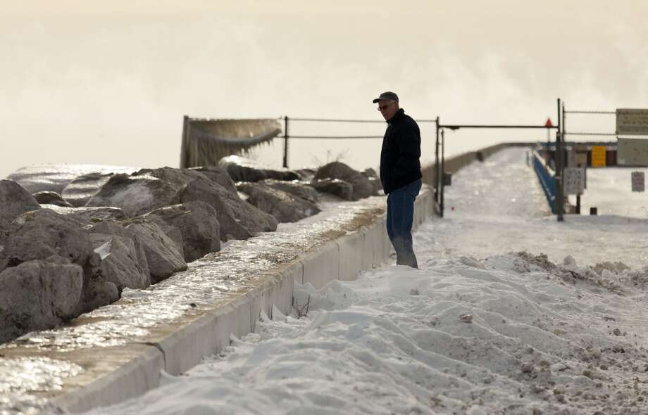 A man braves the cold to check out the icy shore of Lake Michigan as temperatures remain in the negative digits on Jan. 7, 2014 in Milwaukee, Wis. A 'polar vortex' of frigid air centered on the North Pole dropped temperatures to the negative double digits at its worst. (Photo by Darren Hauck/Getty Images) Photo: Darren Hauck, Getty Images