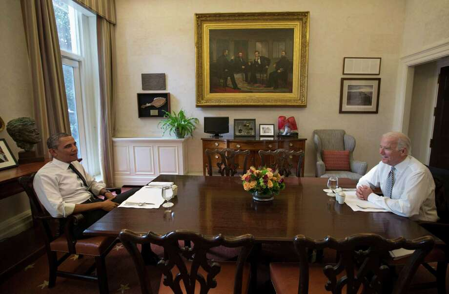 President Barack Obama and Vice President Joe Biden talk during a photo-op as they meet for lunch in the Private Dining Room of the White House in Washington, Wednesday, Jan. 8, 2014. (AP Photo/Carolyn Kaster) Photo: Carolyn Kaster, STF / AP