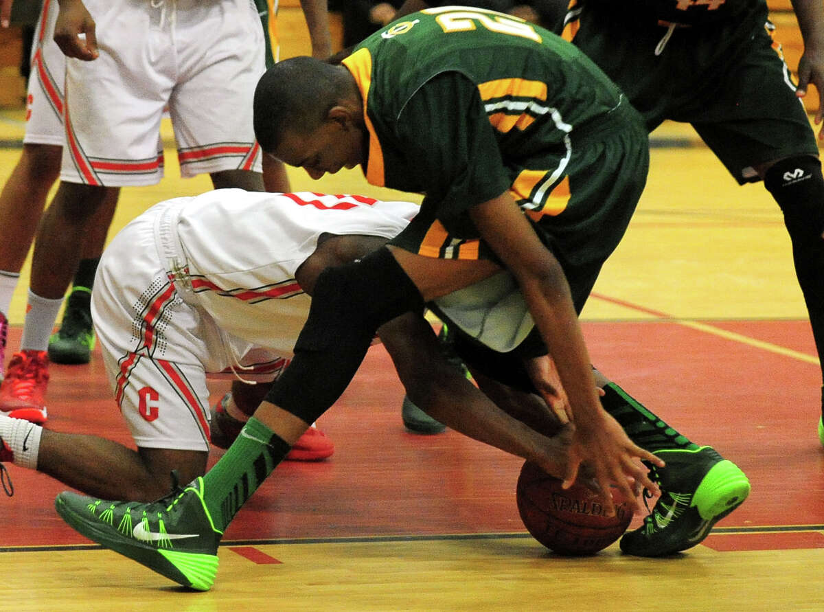 Trinity Catholic's Aaron Wheeler and Central's Tyler Ancrum reach for a loose ball, during boys basketball action in Bridgeport, Conn. on Wednesday January 8, 2014.