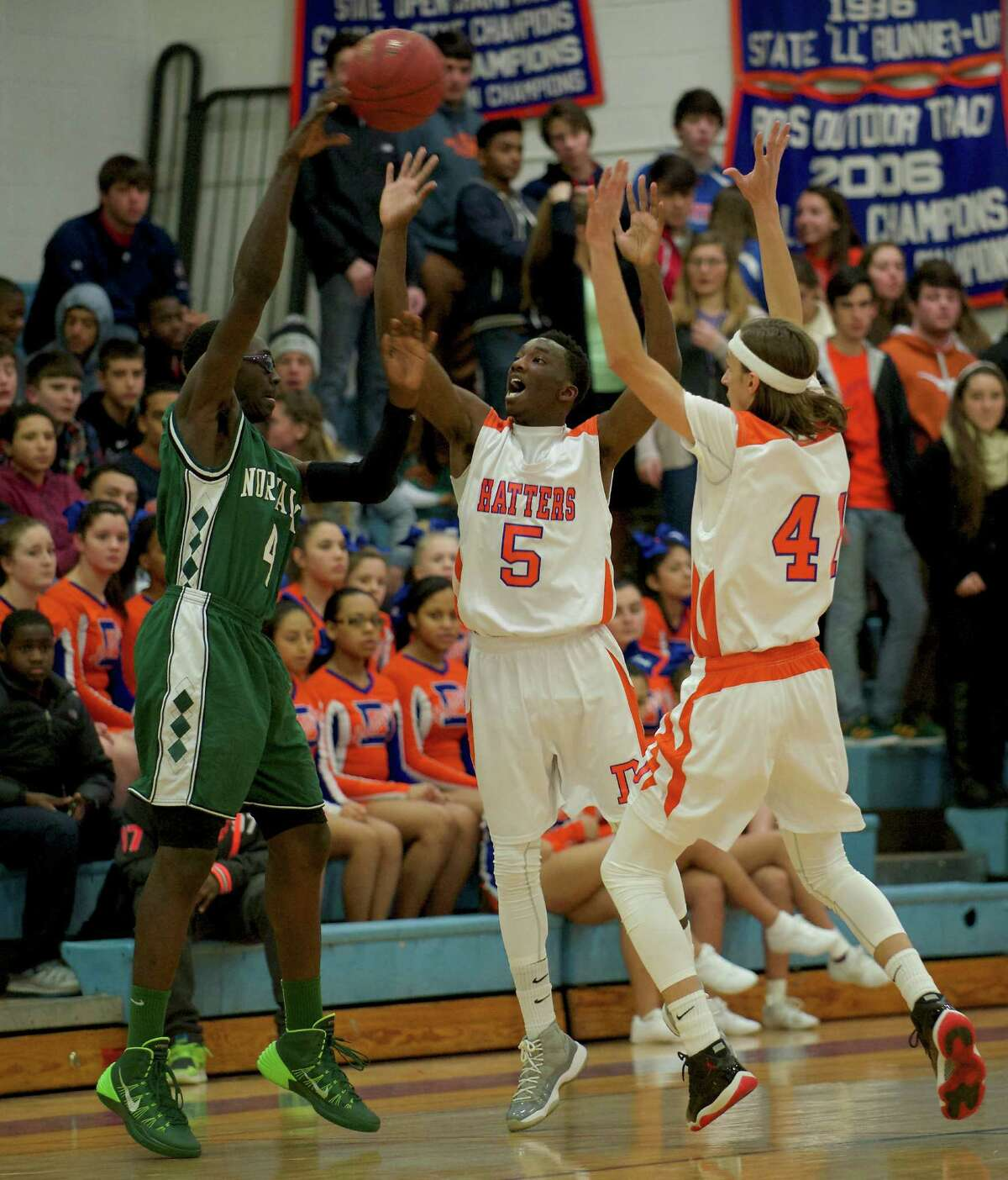 Norwalk's Roy Kane Jr (4) throws a pass over Danbury's C.J. White (5) and Mike Kline (41) during the boys FCIAC basketball game between Norwalk and Danbury high schools played at Danbury High School, Danbury, Conn, on Wednesday, January 8, 2014.