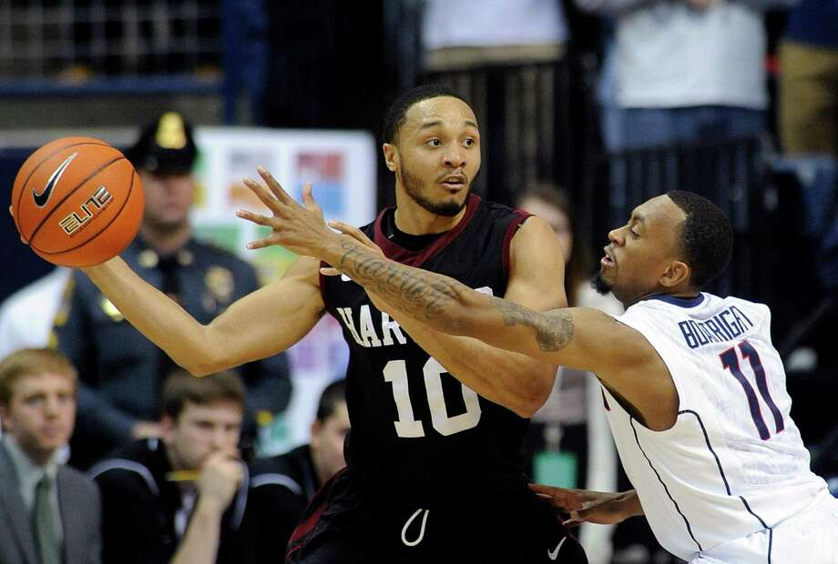 Connecticut's Ryan Boatright (11) guards Harvard's Brandyn Curry (10) during the second half of Connecticut's 61-56 victory in an NCAA college basketball game in Storrs, Conn., Wednesday, Jan. 8, 2014. (AP Photo/Fred Beckham) Photo: Fred Beckham, Associated Press / Associated Press