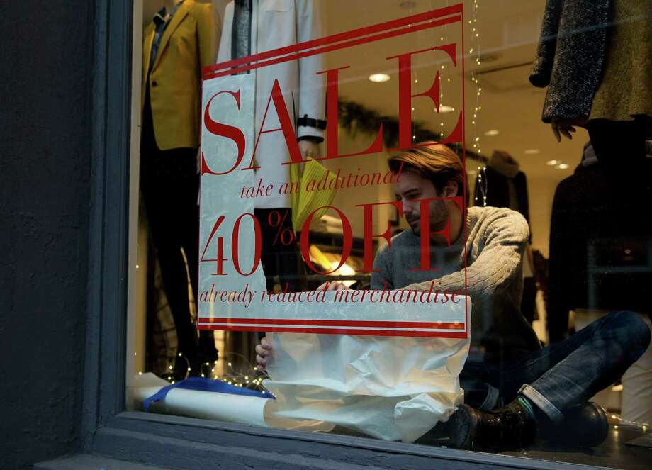 An employee works on a sign in the window of a Club Monaco store in the Soho neighborhood of New York, U.S., on Monday, Dec. 30, 2013. The failure of United Parcel Service Inc. (UPS) and FedEx Corp. to deliver packages in time for Christmas has exposed the perils of retailers promising to get last-minute gifts to customers. Photographer: Jin Lee/Bloomberg Photo: Jin Lee / © 2013 Bloomberg Finance LP