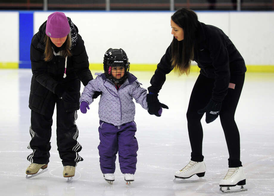 Instructor Jackie Rizzitelli, right, works with young ice skating student Mia Ricca, 3, at the Wonderland of Ice in Bridgeport, Conn. on Wednesday January 8, 2014. At left is Mia's mother Rachael Cuomo-Ricca, who is also an instructor. Photo: Christian Abraham / Connecticut Post