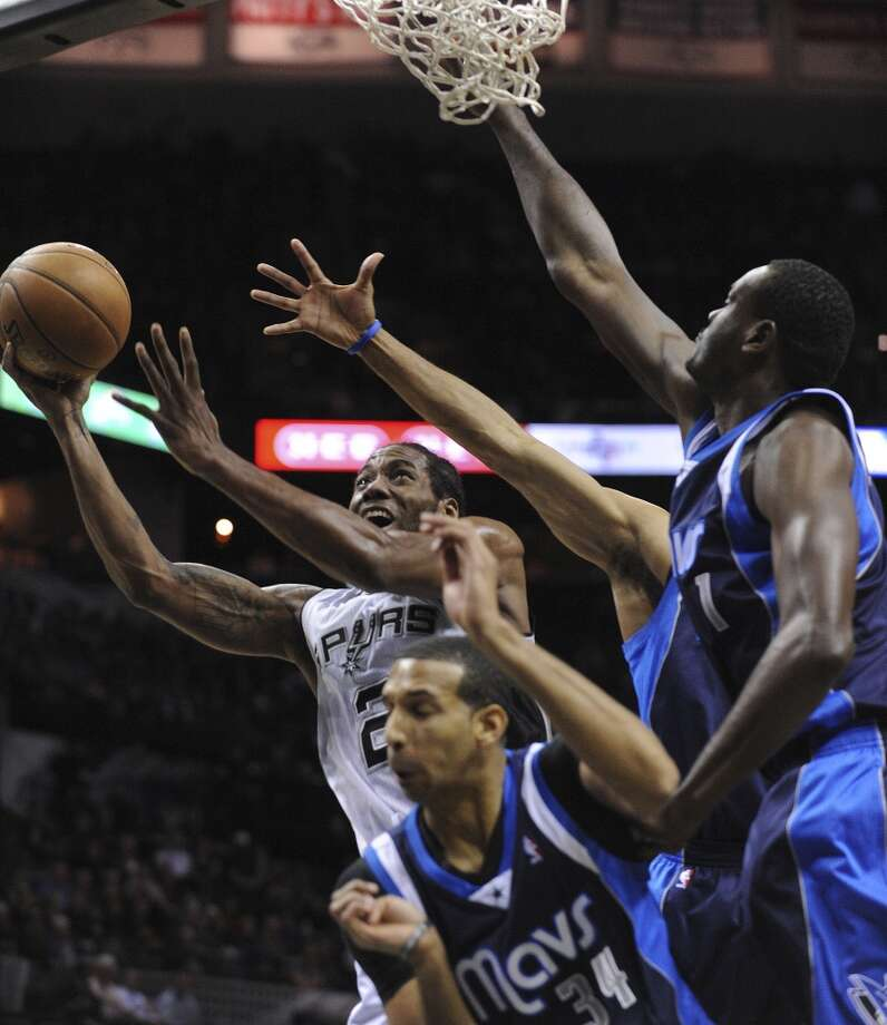 San Antonio Spurs' Kawhi Leonard is fouled as he shoots against Brandan Wright (34) and DaSamuel Dalembert (1) of the Dallas Mavericks during NBA action at the AT&T Center on Wednesday, Jan. 8, 2014. Photo: Billy Calzada, San Antonio Express-News