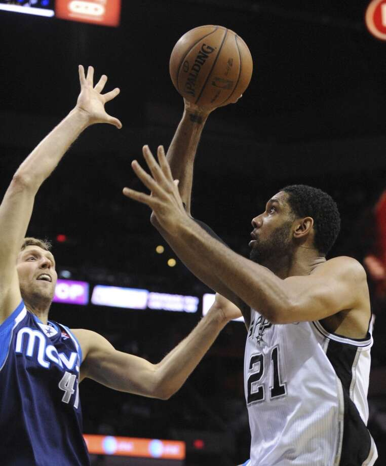 Tim Duncan of the  San Antonio Spurs (21) shoots over the Dallas Mavericks' Dirk Nowitzki (41) during NBA action at the AT&T Center on Wednesday, Jan. 8, 2014. Photo: Billy Calzada, San Antonio Express-News