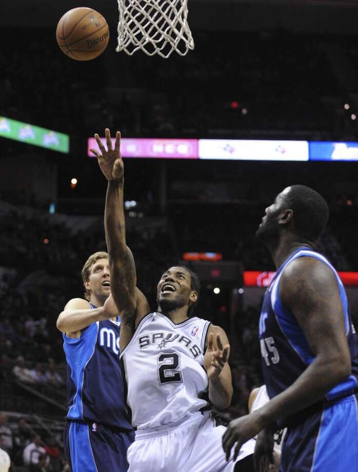 Kawhi Leonard of the San Antonio Spurs (2) shoots and scores after he was fouled by the Dallas Mavericks' DeJuan Blair (45) during NBA action at the AT&T Center on Wednesday, Jan. 8, 2014. Photo: Billy Calzada, San Antonio Express-News