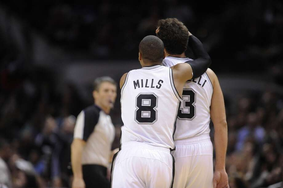 Patty Mills of the San Antonio Spurs embraces teammate Marco Belinelli after Belinelli ran off a series of scores during second-half NBA action at the AT&T Center on Wednesday, Jan. 8, 2014. Belinelli had 17 points as the Spurs defeated the Dallas Mavericks 112-90. Photo: Billy Calzada, San Antonio Express-News