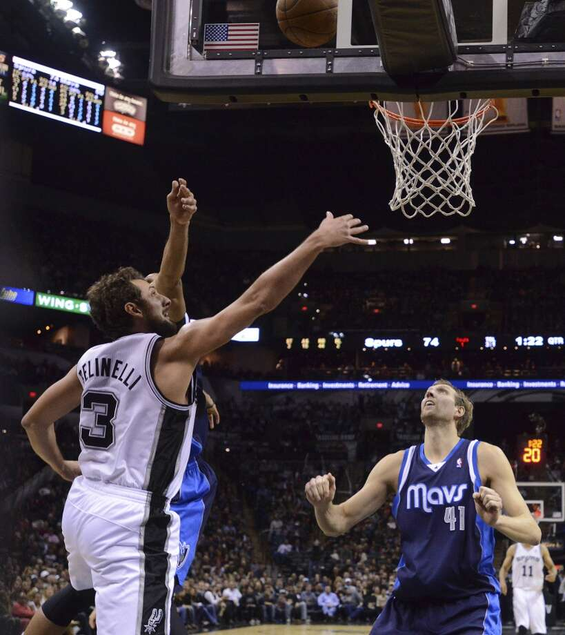 Marco Belinelli of the San Antonio Spurs (3) shoots as the Dallas Mavericks' Dirk Nowitzki (41) watches during second-half NBA action at the AT&T Center on Wednesday, Jan. 8, 2014. Photo: Billy Calzada, San Antonio Express-News