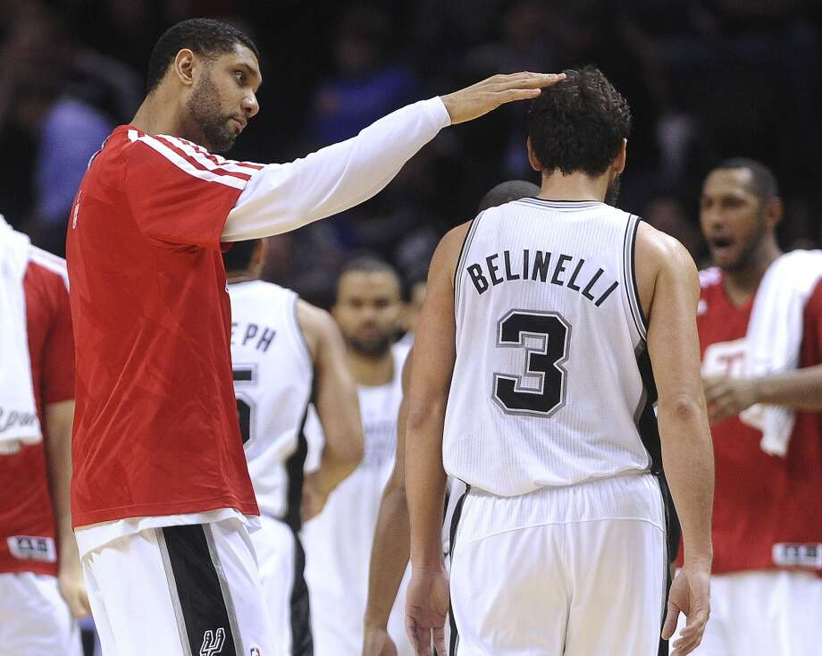 Tim Duncan of the San Antonio Spurs congratulates teammate Marco Belinelli during a time out of team's 112-90 victory over the Dallas Mavericks at the AT&T Center on Wednesday, Jan. 8, 2014. Belinelli scored 17 points in the game. Photo: Billy Calzada, San Antonio Express-News