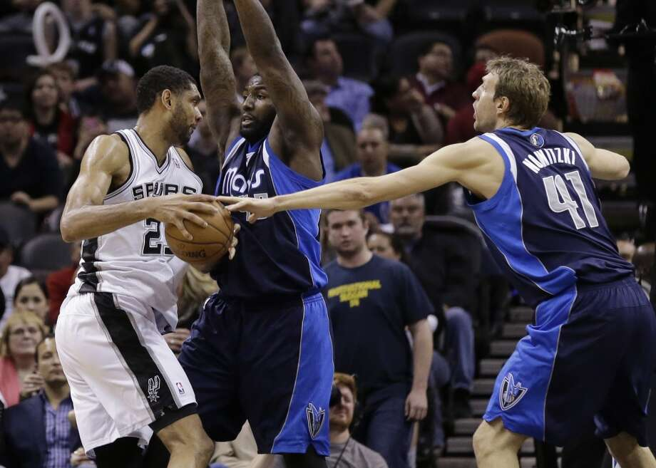 Dallas Mavericks' Dirk Nowitzki (41), of Germany, and DeJuan Blair, center, try to slow down San Antonio Spurs' Tim Duncan during the second half on an NBA basketball game, Wednesday, Jan. 8, 2014, in San Antonio. San Antonio won 112-90. Photo: Eric Gay, Associated Press
