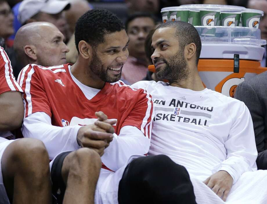 San Antonio Spurs' Tim Duncan, left, and Tony Parker, right, sit on the bench during the second half on an NBA basketball game against the Dallas Mavericks, Wednesday, Jan. 8, 2014, in San Antonio. San Antonio won 112-90. Photo: Eric Gay, Associated Press