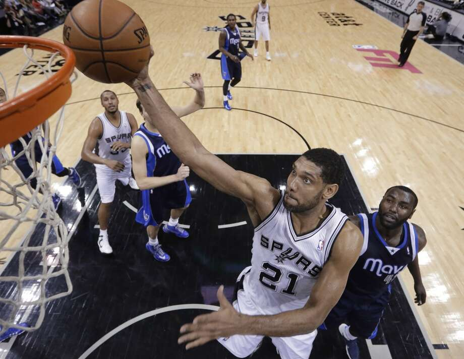 San Antonio Spurs' Tim Duncan (21) scores as Dallas Mavericks' DeJuan Blair (45) watche during the second half on an NBA basketball game, Wednesday, Jan. 8, 2014, in San Antonio. San Antonio won 112-90. Photo: Eric Gay, Associated Press