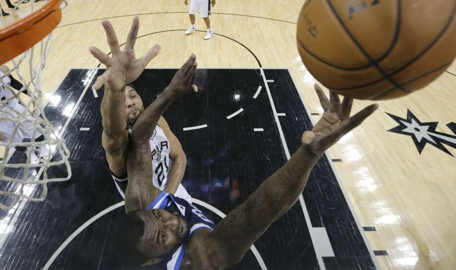 Dallas Mavericks' DeJuan Blair, foreground, shoots as San Antonio Spurs' Tim Duncan defends him during the first half on an NBA basketball game, Wednesday, Jan. 8, 2014, in San Antonio. Photo: Eric Gay, Associated Press