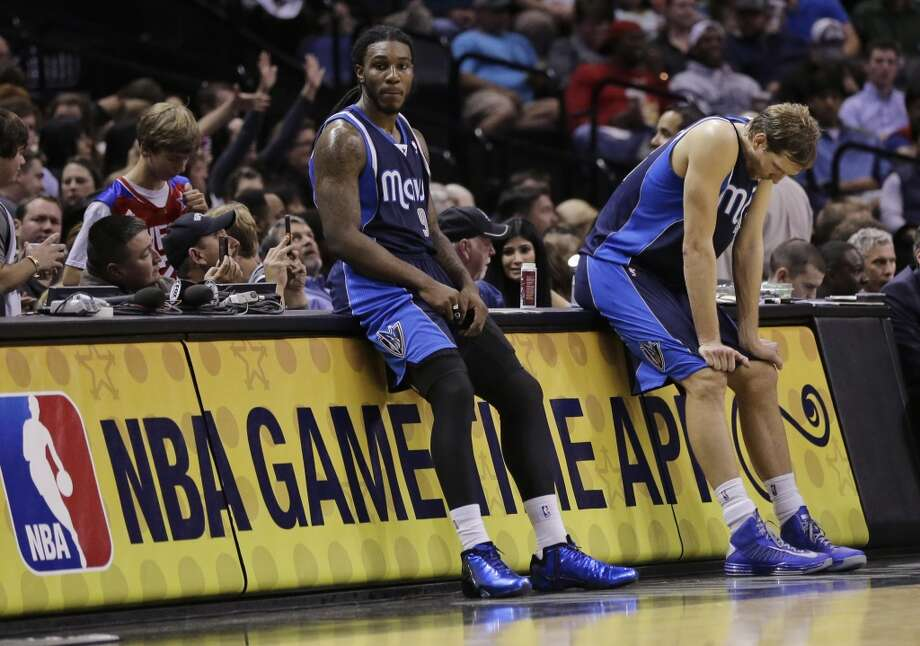 Dallas Mavericks' Jae Crowder (9) and Dirk Nowitzki, right, lean against the scorers' table during a timeout in the second half on an NBA basketball game against the San Antonio Spurs, Wednesday, Jan. 8, 2014, in San Antonio. San Antonio won 112-90. Photo: Eric Gay, Associated Press
