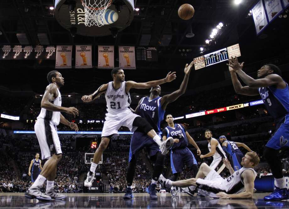 San Antonio Spurs' Tim Duncan (21) and Dallas Mavericks' Samuel Dalembert (1) reach for a rebound during the first half on an NBA basketball game, Wednesday, Jan. 8, 2014, in San Antonio. Photo: Eric Gay, Associated Press