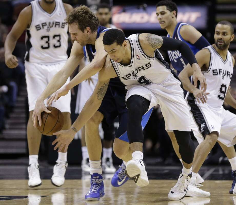 San Antonio Spurs' Danny Green (4) and Dallas Mavericks' Dirk Nowitzki, of Germany, chase a loose ball during the first half on an NBA basketball game, Wednesday, Jan. 8, 2014, in San Antonio. San Antonio won 112-90. Photo: Eric Gay, Associated Press