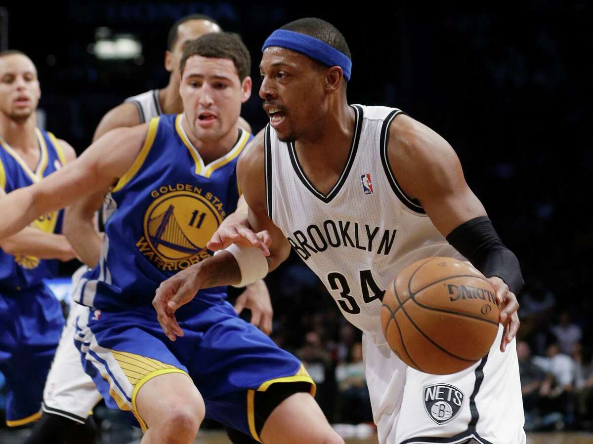Brooklyn Nets' Paul Pierce (34) drives past Golden State Warriors' Klay Thompson (11) during the first half of an NBA basketball game Wednesday, Jan. 8, 2014, in New York. (AP Photo/Frank Franklin II) ORG XMIT: NYFF108