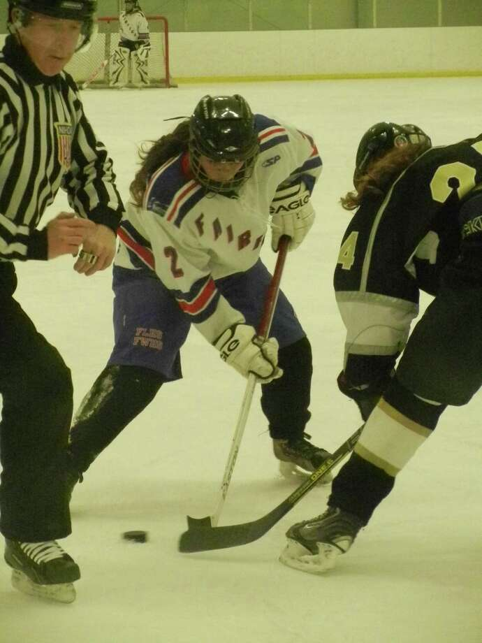 Tabbey Cascella (2), of the Fairfield co-op girls ice hockey team, takes a faceoff on Wednesday, Jan. 8 at the Wonderland of Ice. Trumbull rallied for a 4-3 win in overtime. Photo: Reid L. Walmark / Fairfield Citizen