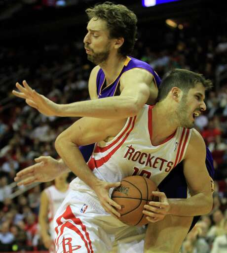 Rockets forward Omri Casspi feels the effects of an elbow from Pau Gasol. Photo: Karen Warren, Staff / © 2013 Houston Chronicle