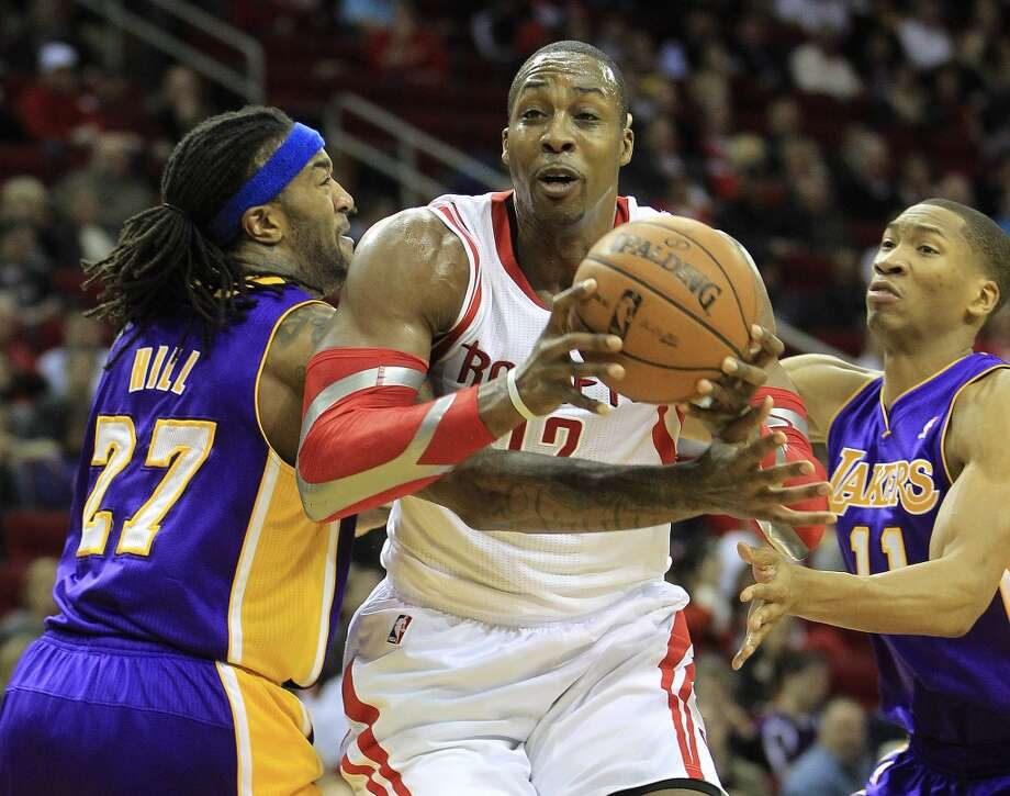 Jan. 8: Rockets 113, Lakers 99  Rockets power forward Dwight Howard (12) tries to get past Lakers center Jordan Hill (27) and shooting guard Wesley Johnson (11) to get to the basket. Photo: Karen Warren, Houston Chronicle