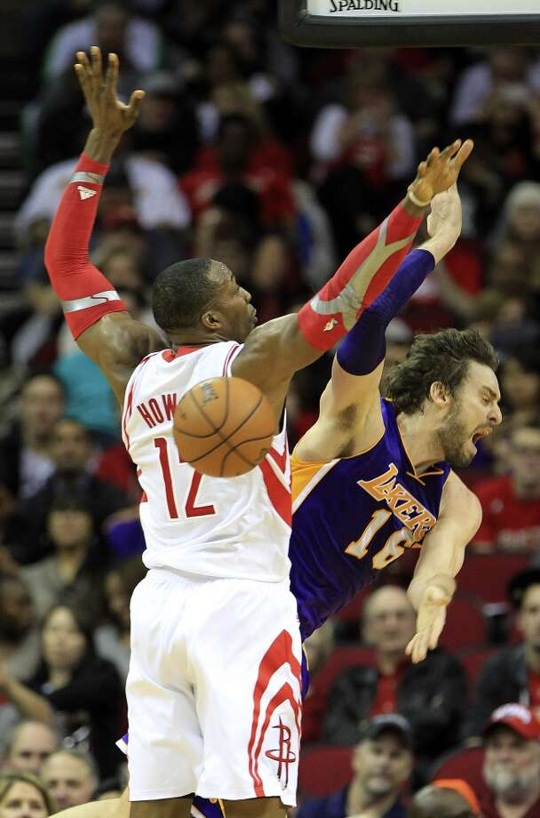 Lakers center Pau Gasol (16) gets tripped up by Rockets power forward Dwight Howard (12) on his way to the basket. Photo: Karen Warren, Houston Chronicle