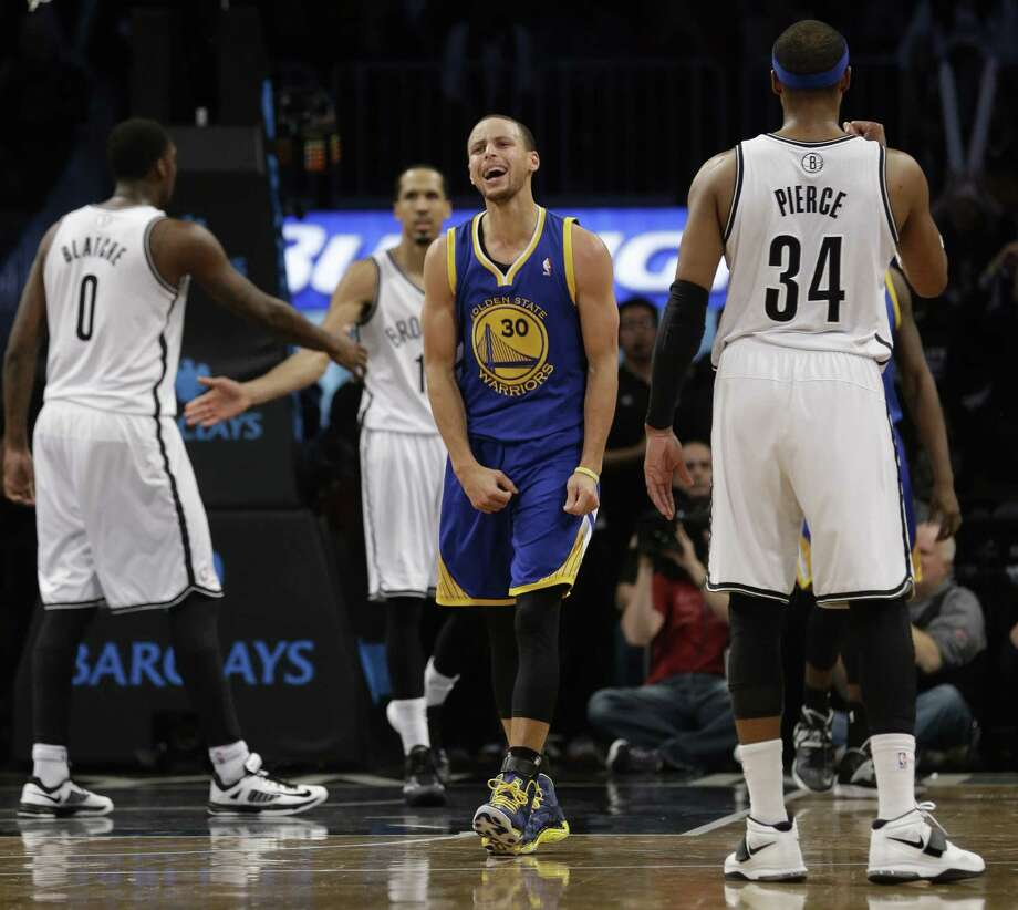Golden State guard Stephen Curry (center) reacts to being called for a foul as Brooklyn's Andray Blatche (left) and Paul Pierce (right) look on. Photo: Frank Franklin II / Associated Press / AP