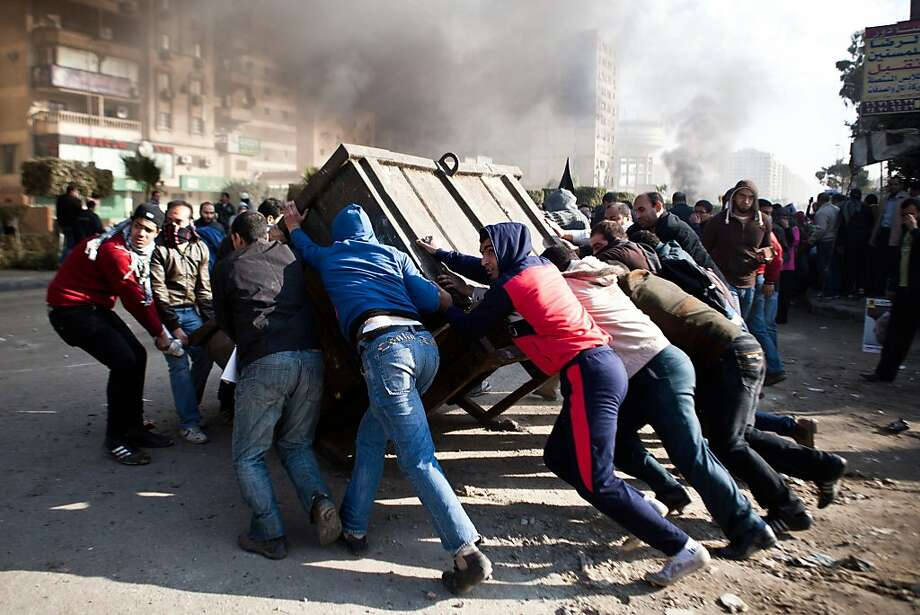 """TOPSHOTS Supporters of ousted president Mohamed Morsi block a street during clashes with Egyptian security forces in Nasr City, Cairo on January 8, 2014. An Egyptian court adjourned the murder trial of deposed president  Morsi to February 1, citing """"weather conditions"""" that prevented the Islamist's transport to court from prison. TOPSHOTS/AFP PHOTO / VIRGINIE NGUYEN HOANGVIRGINIE NGUYEN HOANG/AFP/Getty Images Photo: Virginie Nguyen Hoang, AFP/Getty Images"""