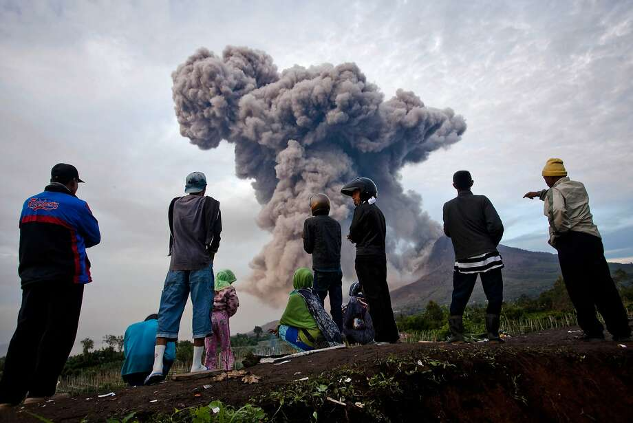 People cluster to watch Mount Sinabung spew smoke. Photo: Ulet Ifansasti, Getty Images