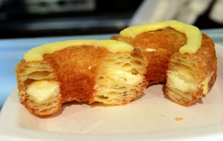 """IN: Hybrid desserts, like the flaky-creamy, croissant-doughnut """"cronut,"""" pictured. Also popular: The """"townie,"""" or a brownie in a tart.  Photo: EMMANUEL DUNAND, Getty Images / 2013 AFP"""