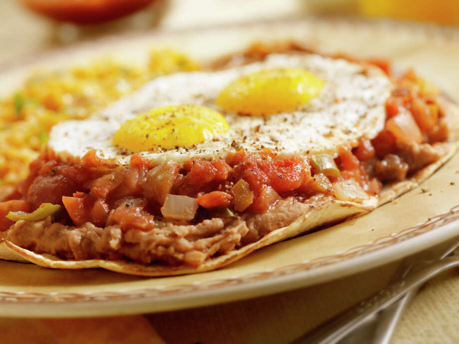 "IN: Ethnic breakfasts, like huevos rancheros, pictured, and ""ethnic-inspired"" breakfasts, like coconut-milk pancakes. Seems like huevos rancheros was such a standard brunch item for years that it now should be ""out.""  Photo: Lauri Patterson, Getty Images / (c) Lauri Patterson"