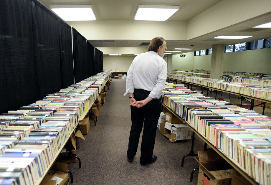 James Shoemaker, branch manager, walks between two tables full of books Wednesday afternoon. The Friends of the Library Book Sale will take place Friday and Saturday at the downtown branch library. About 10,000 items -- including books, magazines, and DVDs -- will be sold off at prices ranging from $.10 to $1. Members of the Friends of the Library will get first crack at the sale on Thursday afternoon from 12-8.
