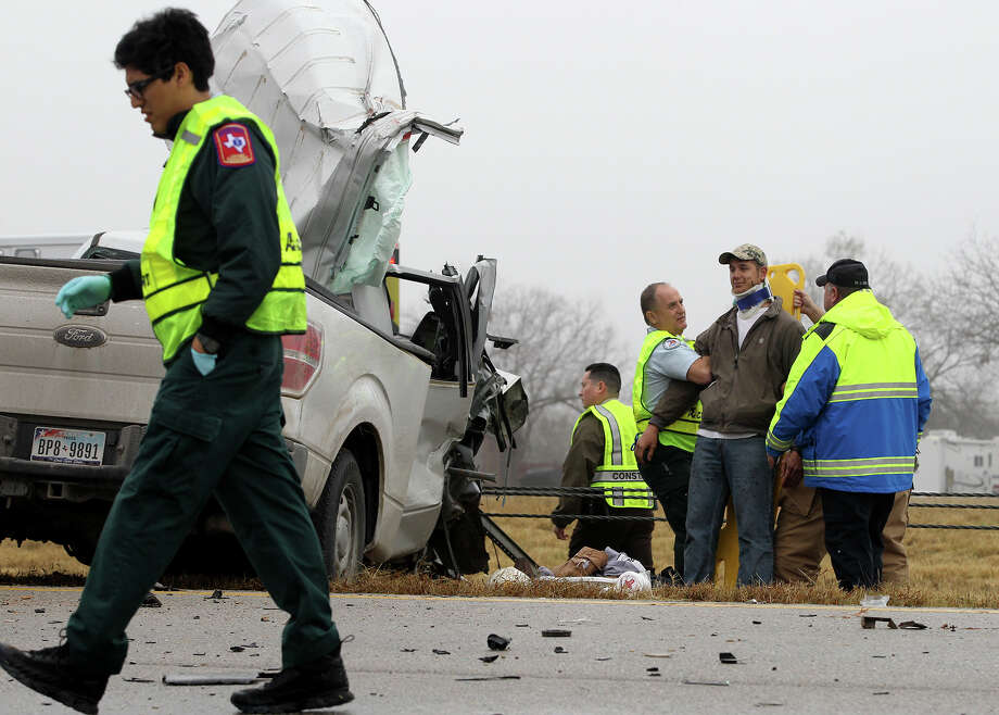 Paramedics tend to an accident victim on I-37 after a multiple vehicle wreck  there under foggy conditions. Photo: John Davenport, San Antonio Express-News / ©