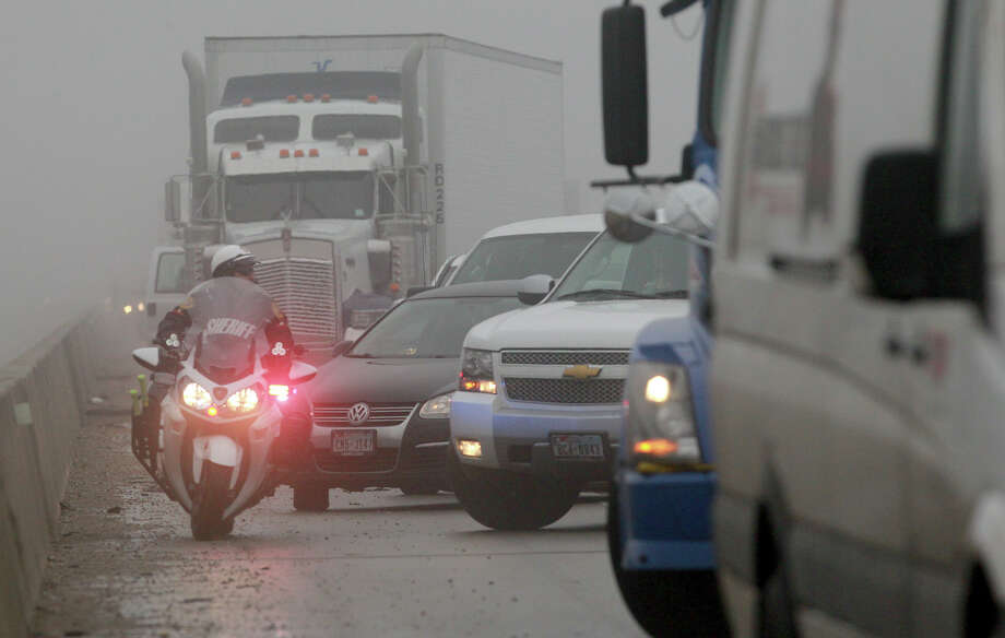 A Bexar County Sheriff's deputy weaves his way through jammed up traffic on I-37 southbound near Loop 1604 after multiple accidents in the area took p[lace under foggy conditions. The interstate was blocked for more than an hour. Photo: JOHN DAVENPORT, SAN ANTONIO EXPRESS-NEWS / ©San Antonio Express-News/Photo may be sold to the public