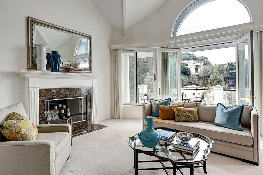 The living room includes a fireplace and French doors opening to a deck. Photo: Liz Rusby/The Grubb Co.