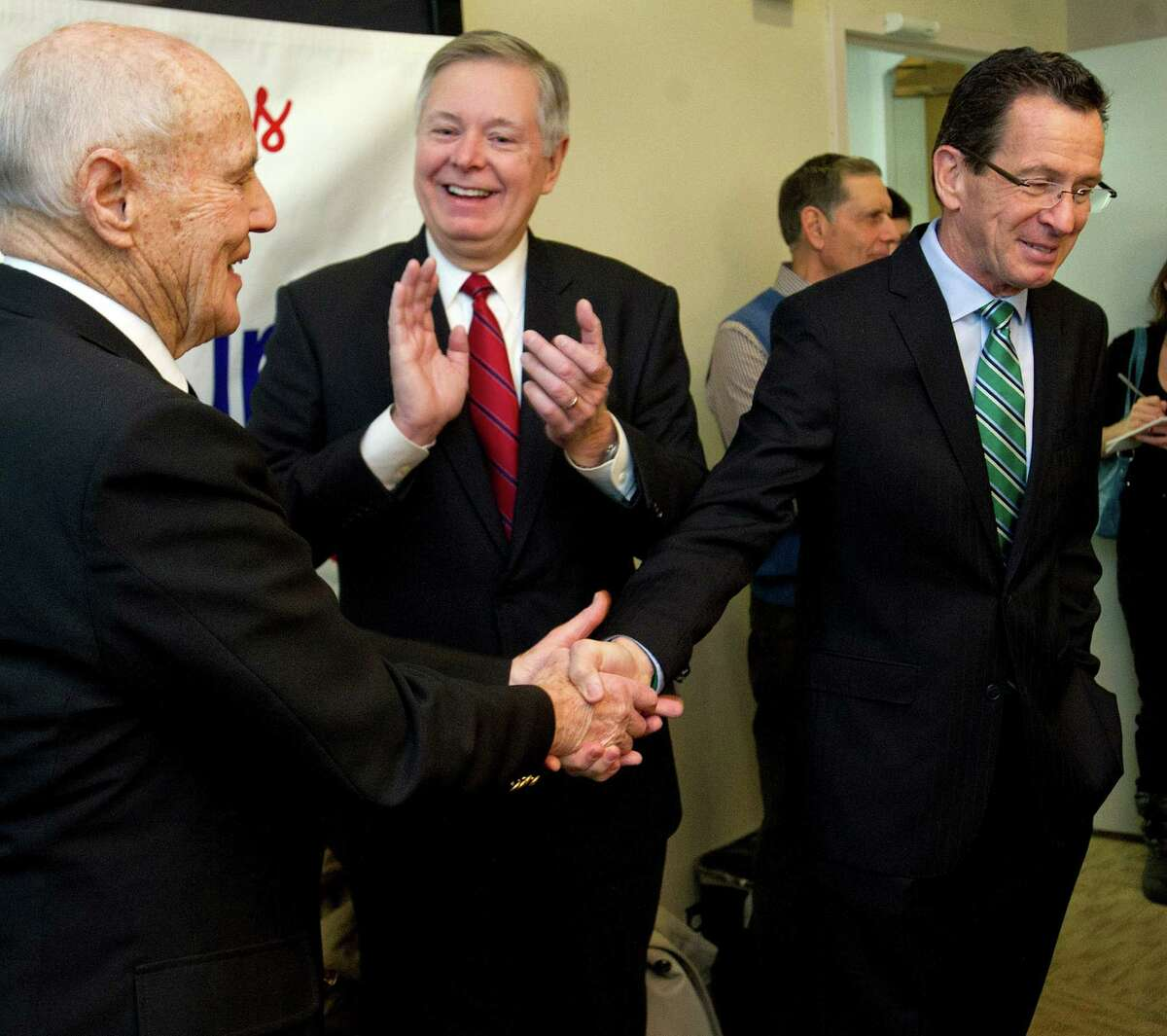 Tim Curtin, special assistant to the mayor, shakes hands with Governor Dannel Malloy as Mayor David Martin looks on. Curtin was surprised with a ceremony to name him the Citizen of the Year at Government Center in Stamford, Conn., on Thursday, January 9, 2014.