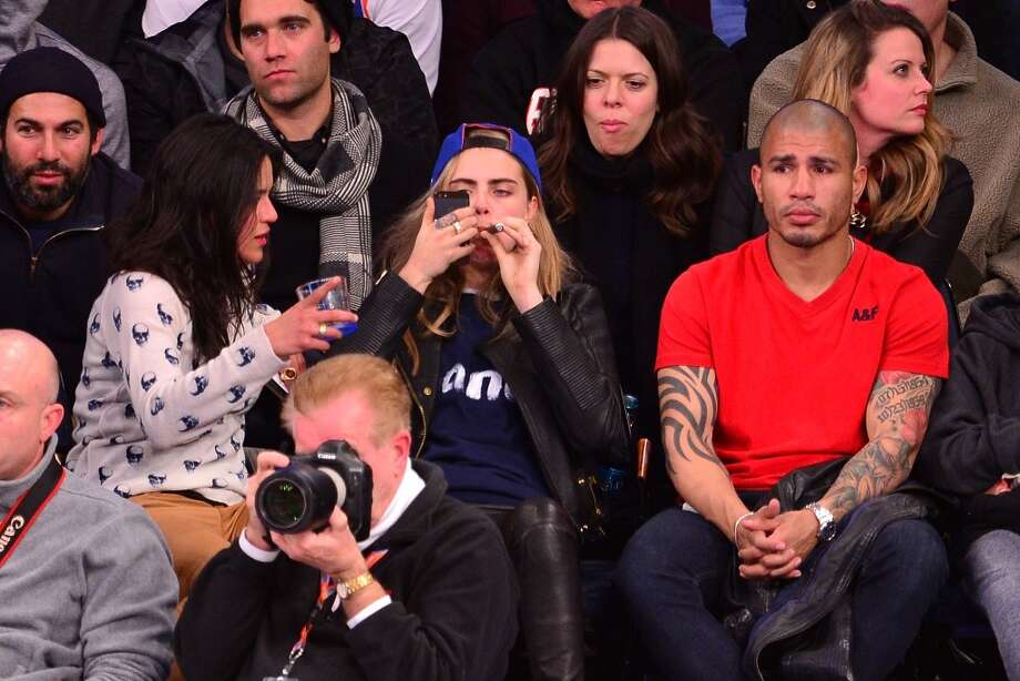 Michelle Rodriguez, Cara Delevingne and Miguel Cotto attend the Detroit Pistons vs New York Knicks game at Madison Square Garden on January 7, 2014 in New York City. Photo: James Devaney, FilmMagic