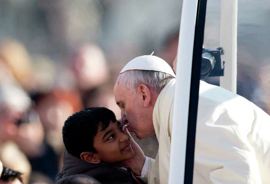 Pope Francis greets a child Wednesday during his weekly general audience in St. Peter's Square. Photo: Alessandra Tarantino, STF / AP