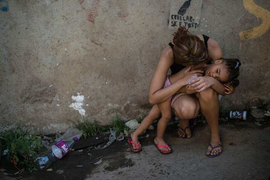 A mother holds her child at Metro favela, a shantytown near Maracana Stadium in Rio de Janeiro. Brazil is demolishing the homes of hundreds of favela residents before this year's World Cup. Those who do not accept compensation are reportedly being forced out. Photo: Yasuyoshi Chiba, AFP/Getty Images