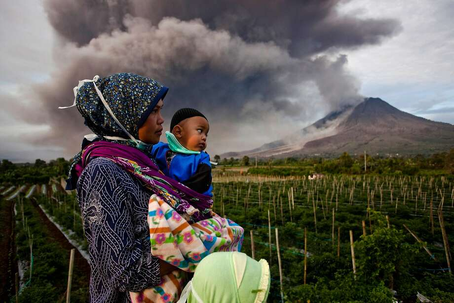 Still erupting:A villager and her son watch Mount Sinabung spew pyroclastic smoke in Karo District, North Sumatra. More than 22,000   people have been forced from their homes by the volcano in Western Indonesia. Photo: Ulet Ifansasti, Getty Images