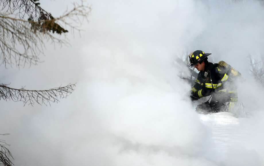 Smoke engulfs a firefighter on the roof of a burning house in South Elgin, Ill. A man and a dog died in the blaze, while his wife and another dog were rescued. Authorities suspect the careless use of smoking materials was the cause of the fire. Photo: Rick West, Associated Press