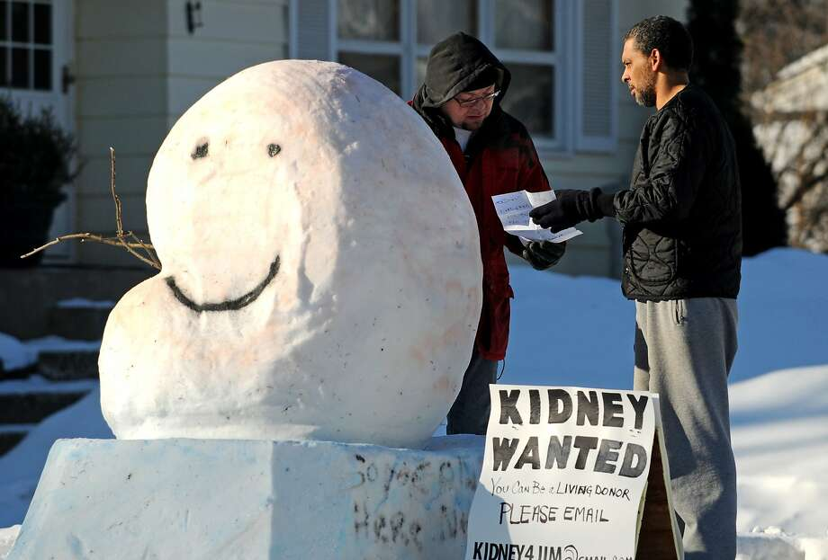 "Frosty the Kidney:Jim Gorbunow (left), who desperately needs a kidney, built a smiling ""snow kidney"" at his home in Cottage Grove, Minn., in hope of attracting a donor. Here he explains his situation to Louis Benejam. Photo: Jean Pieri, Associated Press"