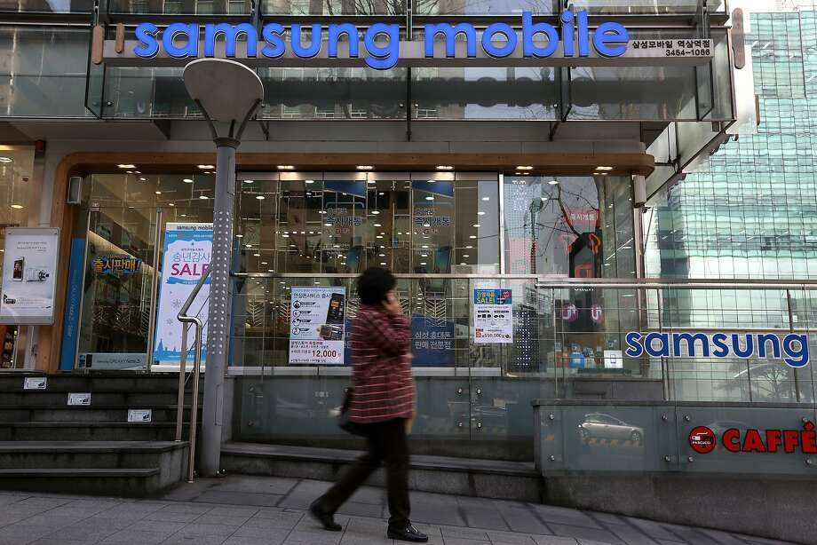 A woman chats on her mobile phone near a Samsung store in Seoul. The South Korea company will discuss a settlement of the Apple suit against it. Photo: SeongJoon Cho, Bloomberg