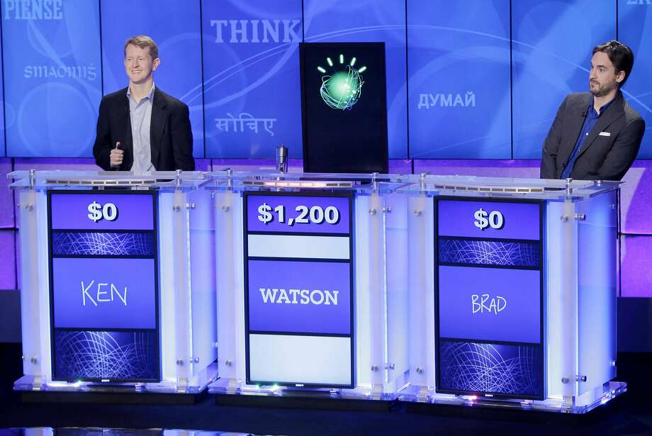 "FILE - In this file photo of  Jan. 13, 2011, ""Jeopardy!"" champions Ken Jennings, left, and Brad Rutter, right, look on as the IBM computer called ""Watson"" beats them to the buzzer to answer a question during a practice round of the ""Jeopardy!"" quiz show in Yorktown Heights, N.Y. IBM announced Thursday, Jan. 9, 2014  that it's investing over $1 billion to give its Watson cloud computing system its own business division and a new home in the heart of New York City  (AP Photo/Seth Wenig, File) Photo: Seth Wenig, Associated Press"