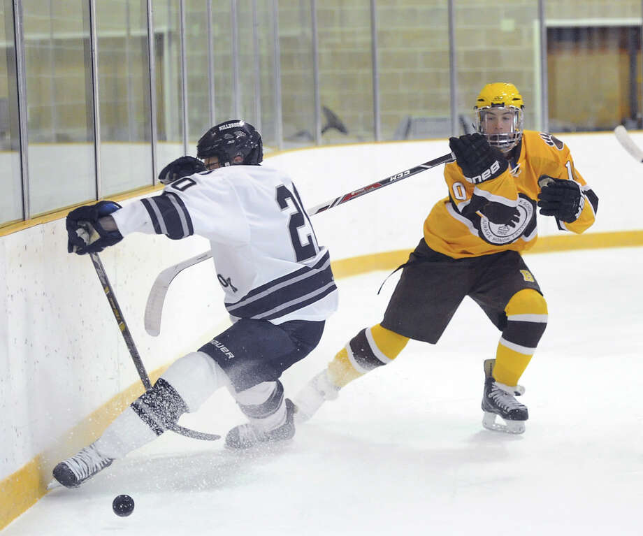 At right, Brunswick's Colin Slyne (#10) goes for a loose puck against Millbrook's Lake Miller (#20) during the boys high school ice hockey game between Brunswick School and Millbrook School at Brunswick in Greenwich, Wednesday afternoon, Jan. 8, 2014. Photo: Bob Luckey / Greenwich Time
