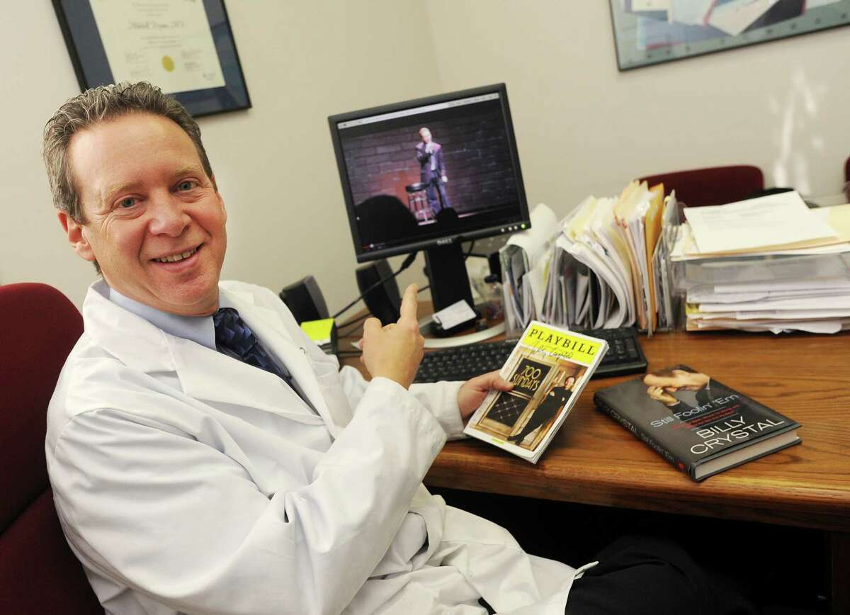 Danbury Physician, Dr. Mitchell Prywes photographed in his Danbury, Conn. office on Thursday Jan. 9, 2014. Prywes performed his stand-up comic routine at The Ridgefield Playhouse as part of the Christine O'Leary workshop on Nov. 24, 2013, just two days after meeting Billy Crystal in New York City. A YouTube video of Prywes' act is on the computer screen behind him.