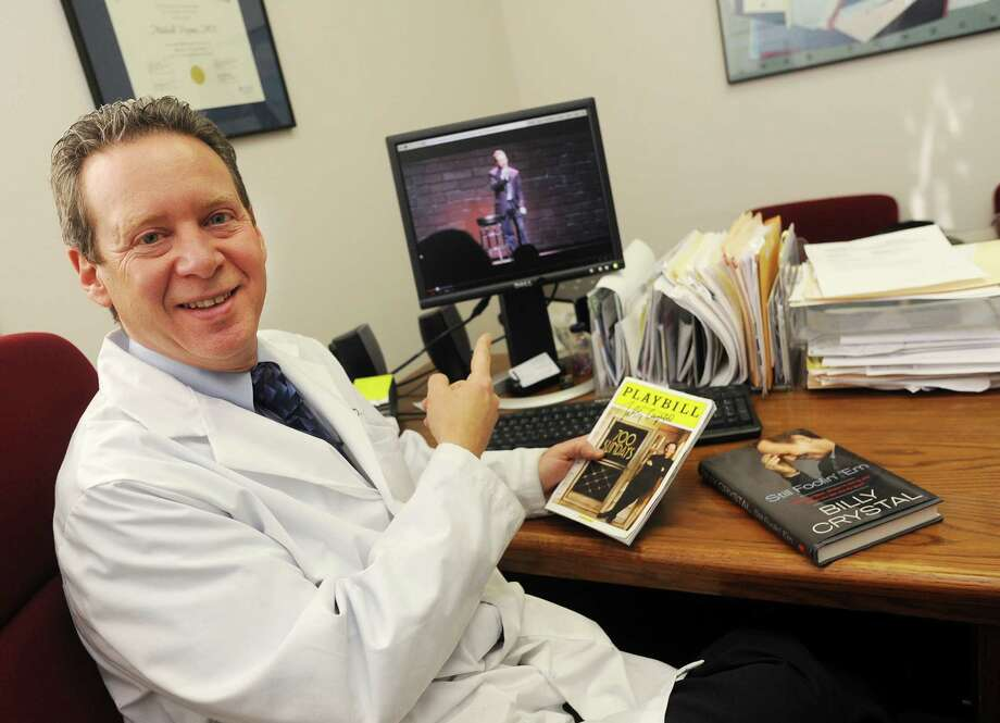 Danbury Physician, Dr. Mitchell Prywes photographed in his Danbury, Conn. office on Thursday Jan. 9, 2014. Prywes performed his stand-up comic routine at The Ridgefield Playhouse as part of the Christine O'Leary workshop on Nov. 24, 2013, just two days after meeting Billy Crystal in New York City. A YouTube video of Prywes' act is on the computer screen behind him. Photo: Cathy Zuraw / The News-Times